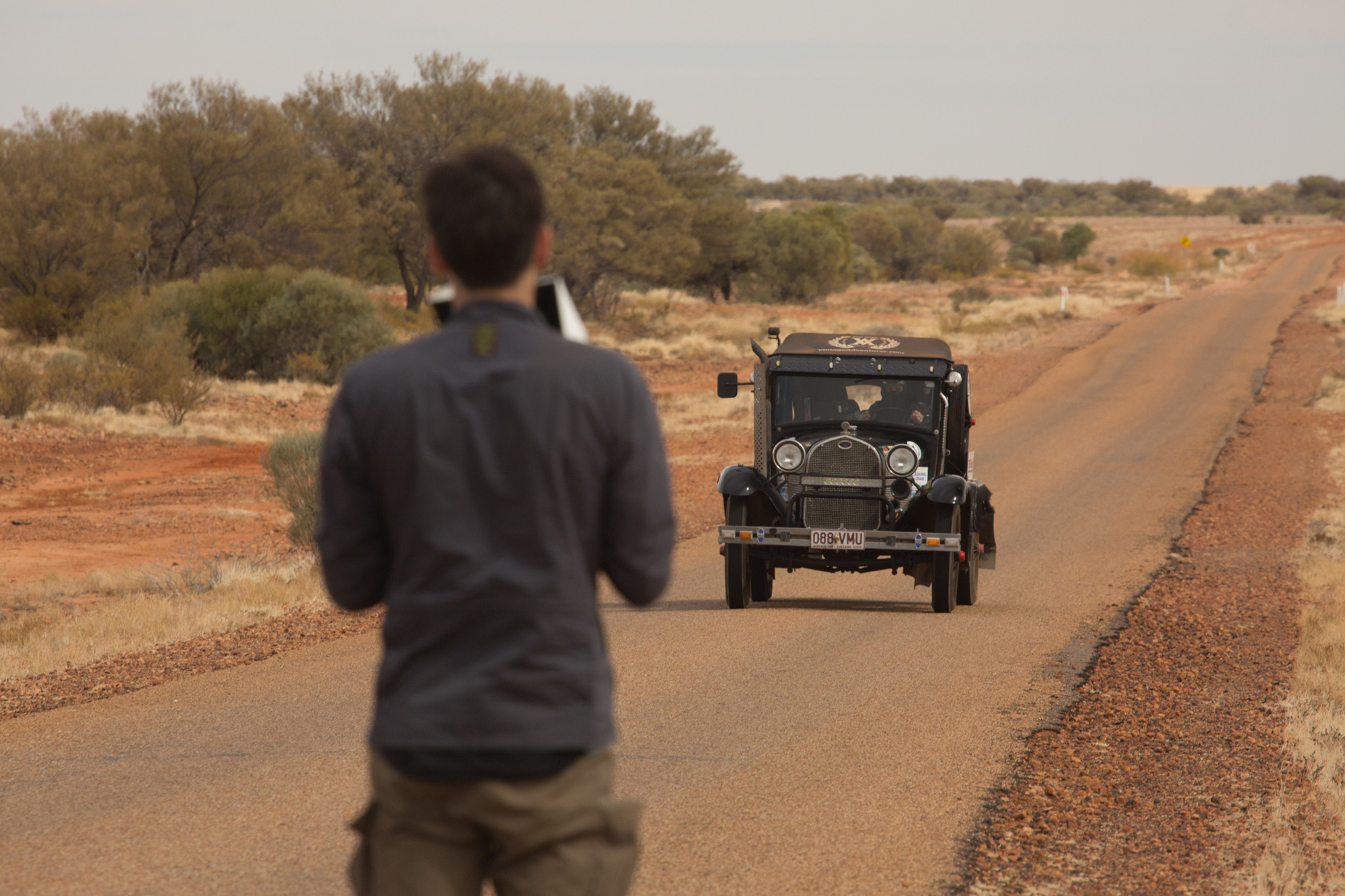 Ben Sherlock filming vehicle on road in Australia