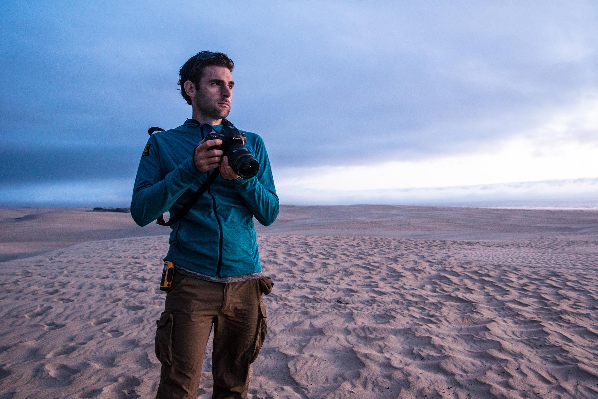 Ben Sherlock standing with camera in Australian desert
